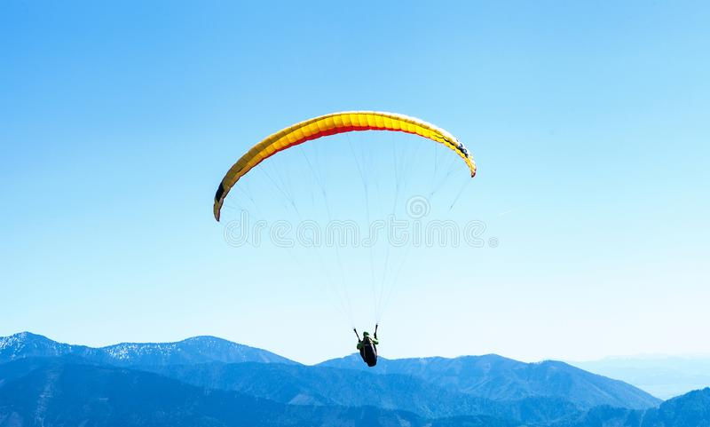 Paraglider soaring in the sky over the blue mountains stock photography