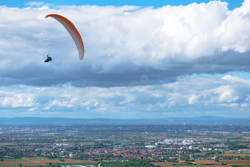 Paraglider som flyger över fält och städer arkivfoto