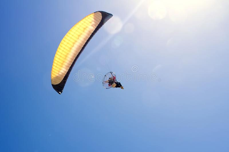 Paraglider in yellow paraglider flying toward sun in stock photo