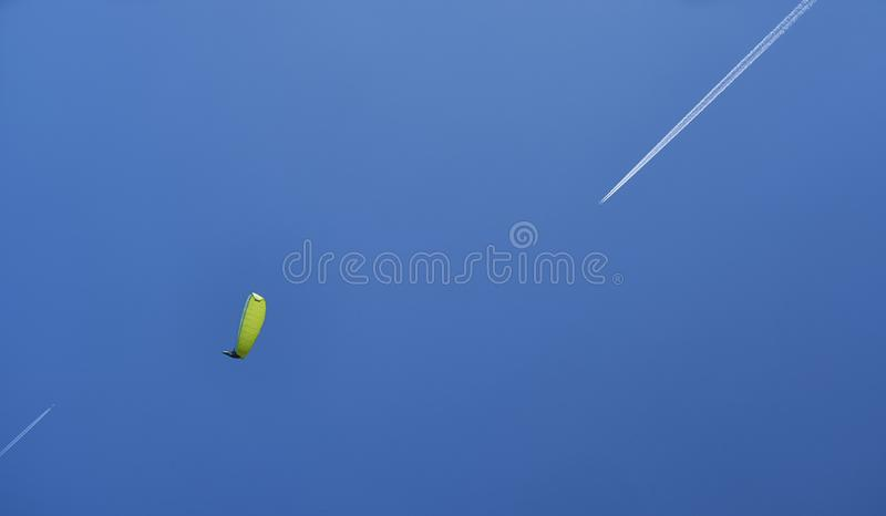 A paraglider with a yellow-green parashute and two airplanes. royalty free stock images