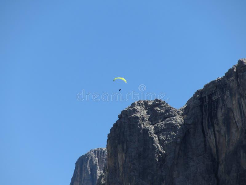 Paraglider z jego żółtymi spadochronowymi latającymi pobliskimi wysokimi włoskimi górami Dolomity, Włochy zdjęcie royalty free