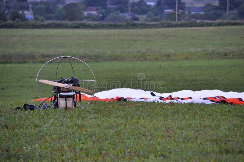 Paraglideren efter flygställningarna på det gröna gräset i fältet, kupolen och vingen fälls ned till jordningen fotografering för bildbyråer