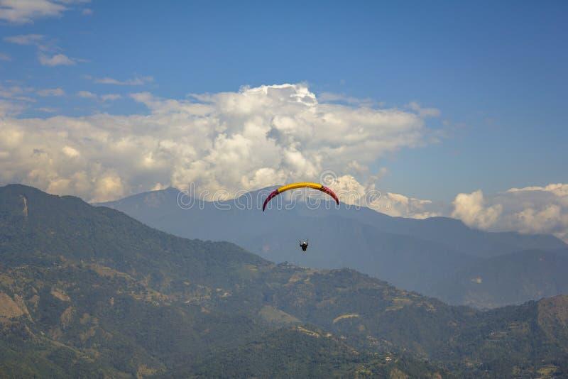 Paraglideren på enguling hoppa fallskärm flugor mot en bakgrund av gröna berg och vita moln i den blåa himlen, flyg- sikt royaltyfria foton