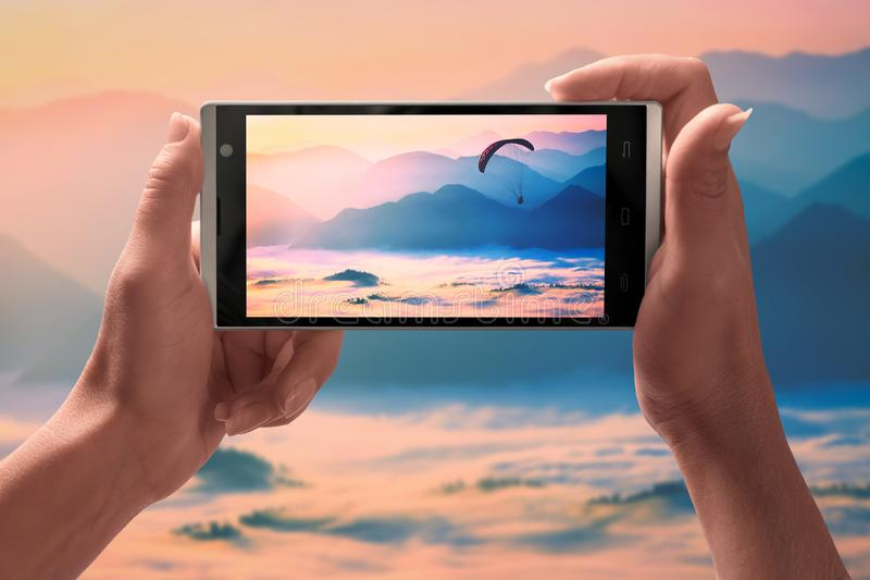 Paragliderflyg över bergen på en skärm av smartphonen royaltyfri bild