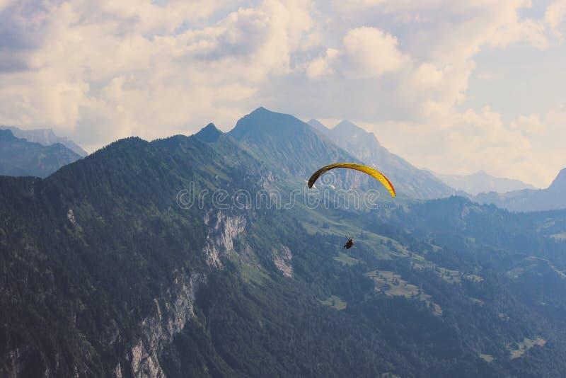 Paragliders över schweiziska fjällängar i sommar Dåligt väder risk, farabegrepp Extrema sportar, affärsföretaglivsstil switzerlan royaltyfria bilder