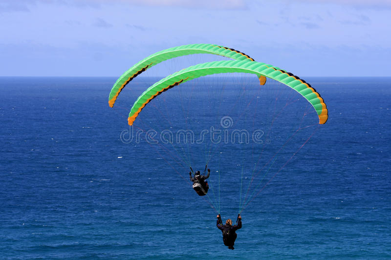 Paragliders above the sea. Paragliders flying over the sea stock photos