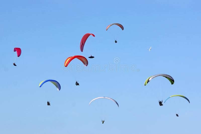 Paragliders in a blue sky. Paragliders flying coloured wings in a blue sky royalty free stock photography