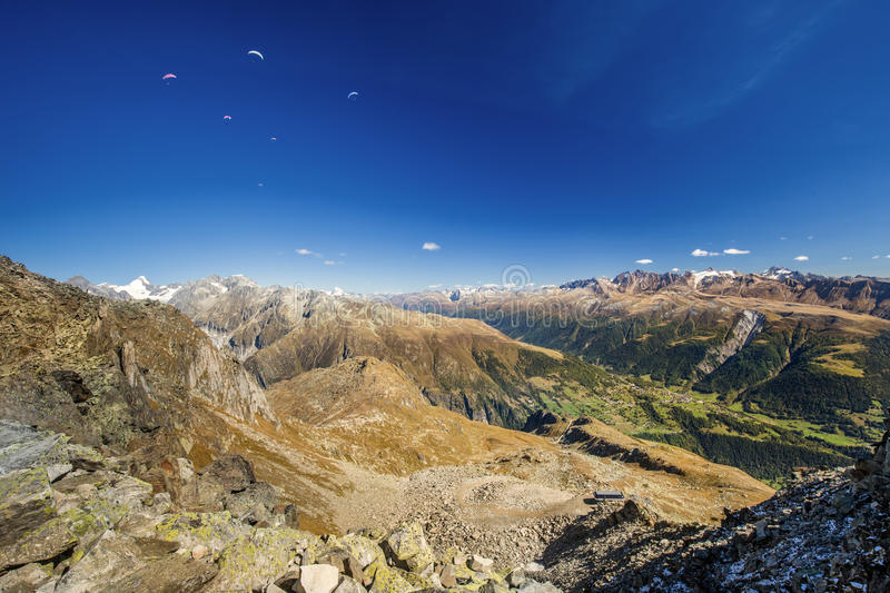 Paragliders enjoying majestic view to Swiss Alps from the top of stock photography