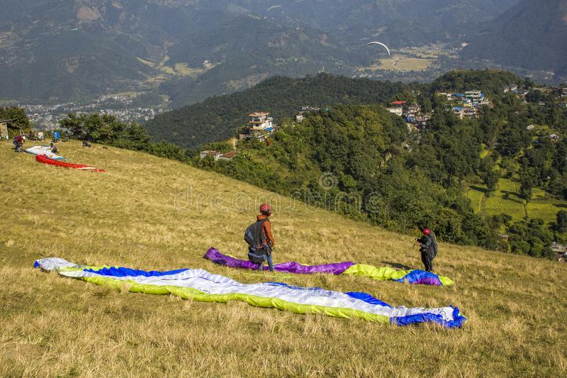Paragliders on the mountainside prepare to take off on the background of green mountains and houses in royalty free stock photography