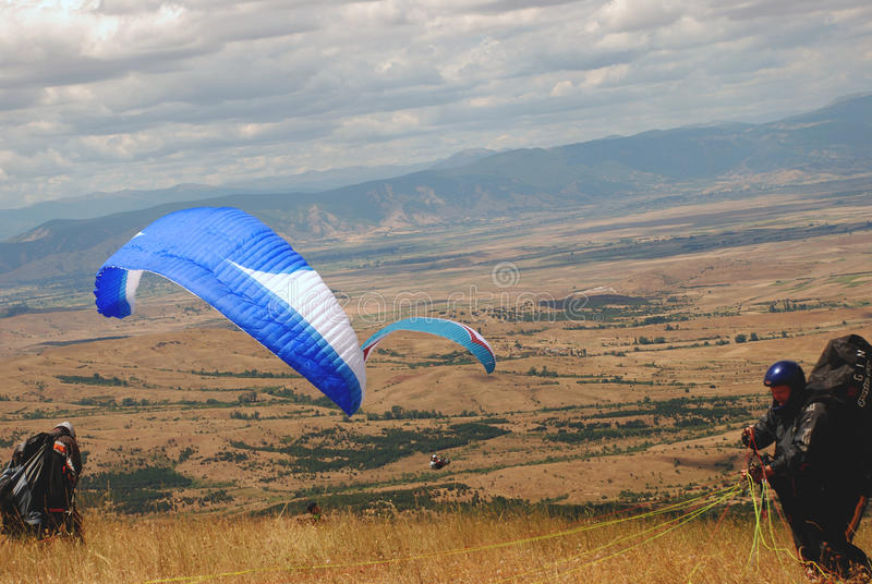 Paragliders in the preparation for start stock image