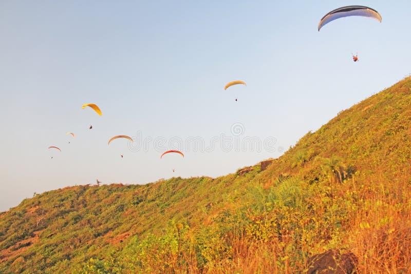 Paragliders przeciw niebieskiemu niebu Jaskrawi paragliders latają w obraz royalty free