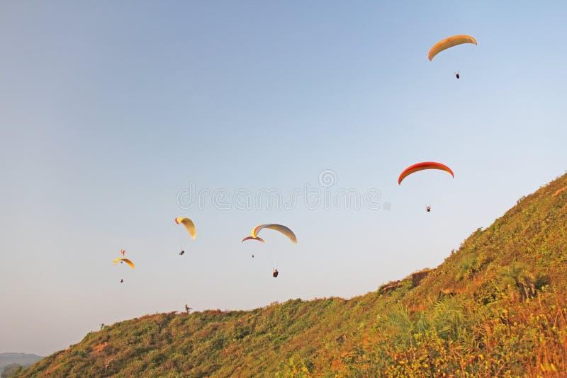 Paragliders przeciw niebieskiemu niebu Jaskrawi paragliders latają w obraz stock