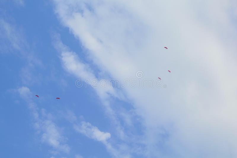 Paragliders in the summer sky. Paragliding photo for background. Summer extreme sports. Mountains and blue sky with clouds. royalty free stock photography