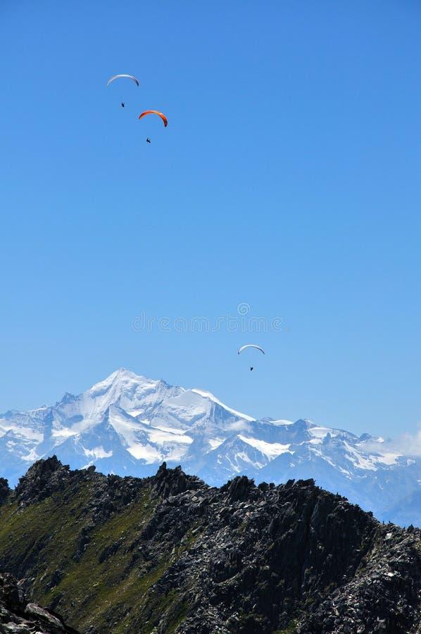 Paragliding över fjällängar royaltyfria foton