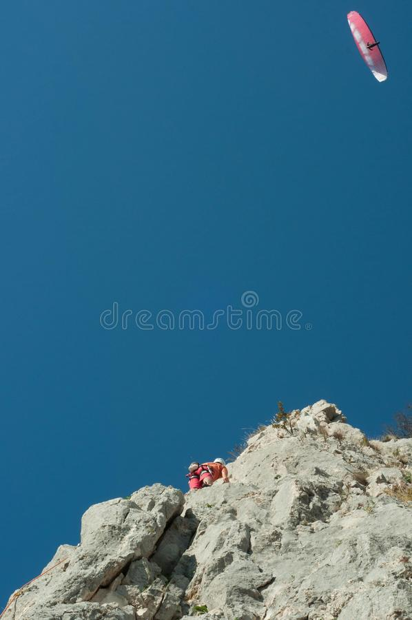 Paragliding and climbing. Paragliding and rock climbing, where the sky meets the ground, worlds coliding stock photography