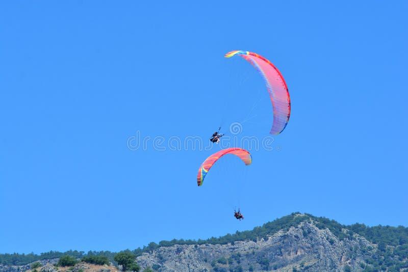 paragliding Dos alas flexibles en un fondo del cielo azul y de las montañas foto de archivo