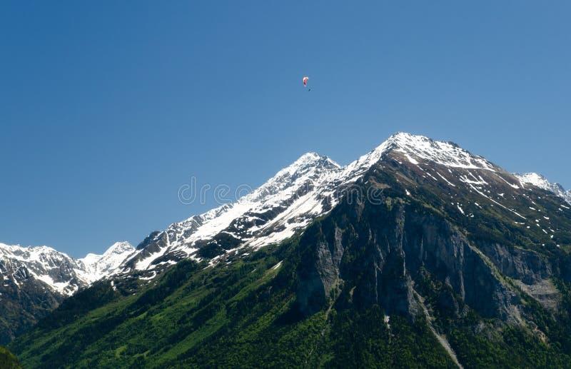 Paragliding en las montañas suizas sobre picos nevados imagen de archivo libre de regalías