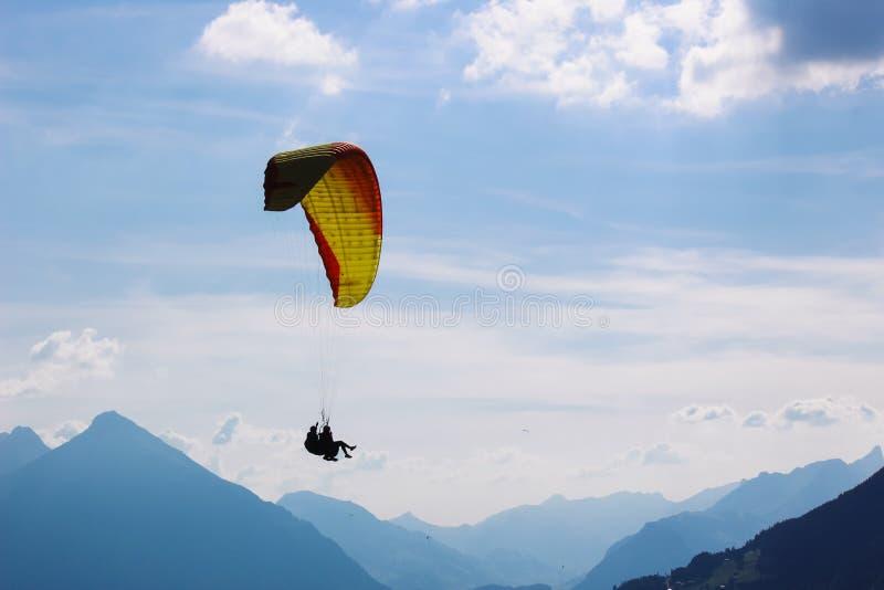 Paragliding en tándem en las montañas suizas Siluetas de alas flexibles y de montañas hermosas Deporte extremo, deportes de la av imágenes de archivo libres de regalías