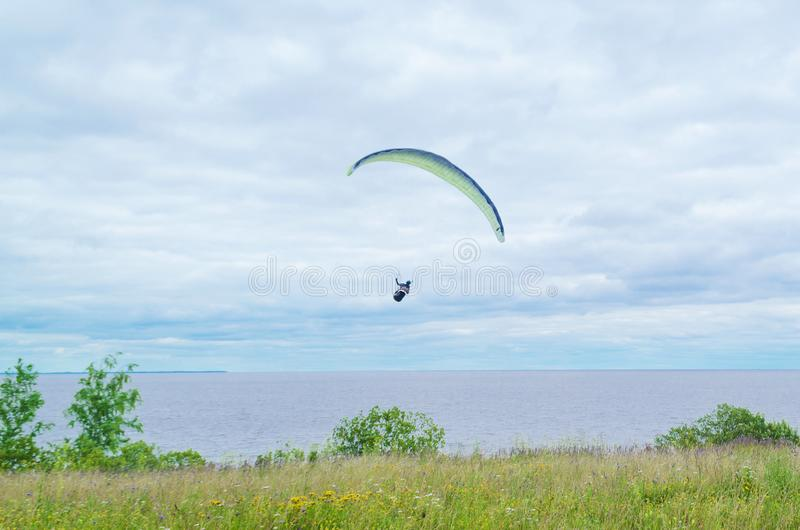 Paragliding Extreme Sport Concept. A paraglider flies in the sky in a cocoon suit on a paraglider against the sky and clouds. royalty free stock photography