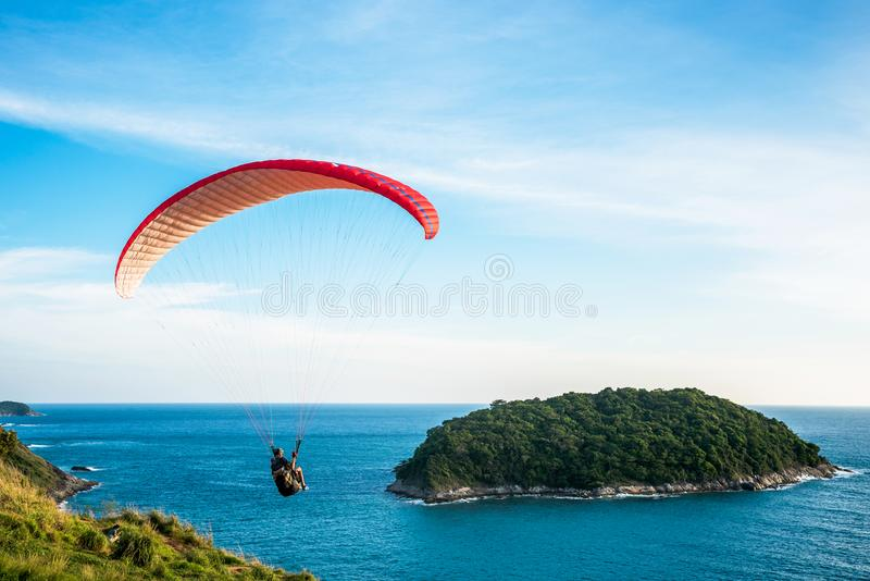 Paragliding Extreme sport, Paraglider flying on the blue sky and white cloud in Summer day at Phuket Sea, Thailand stock image