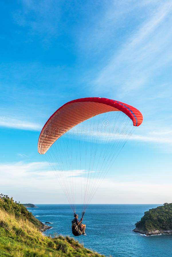 Paragliding Extreme sport, Paraglider flying on the blue sky and white cloud in Summer day at Phuket Sea, Thailand royalty free stock photo