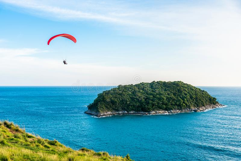 Paragliding Extreme sport, Paraglider flying on the blue sky and white cloud in Summer day at Phuket Sea, Thailand royalty free stock photography