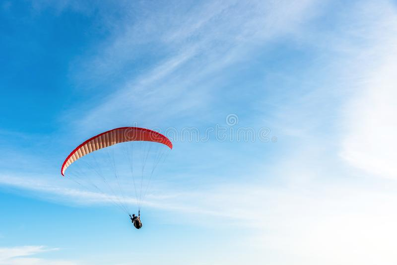 Paragliding Extreme sport, Paraglider flying on the blue sky and white cloud in Summer day at Phuket Sea, Thailand royalty free stock image