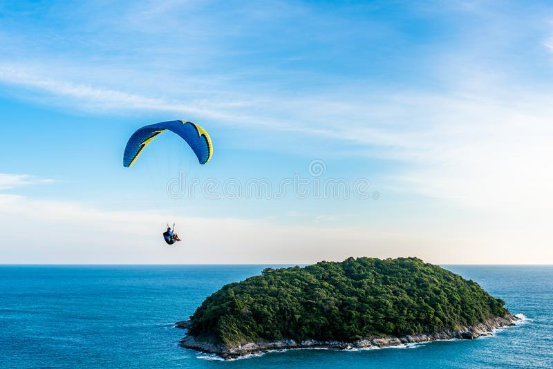Paragliding Extreme sport, Paraglider flying on the blue sky and white cloud in Summer day at Phuket Sea, Thailand stock photography