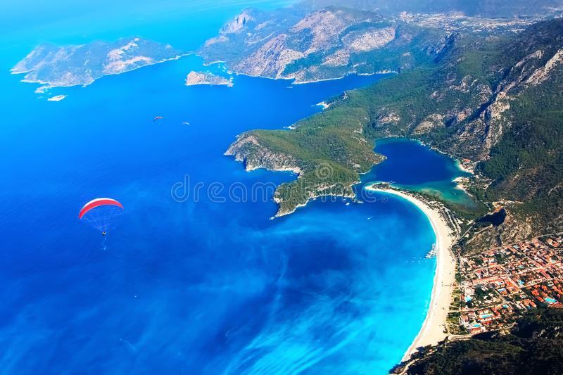 Paragliding flight over the blue lagoon of the Mediterranean Sea. Red dome of the parachute against the blue sea. Turkey. Oludeniz. Aerial photography royalty free stock image