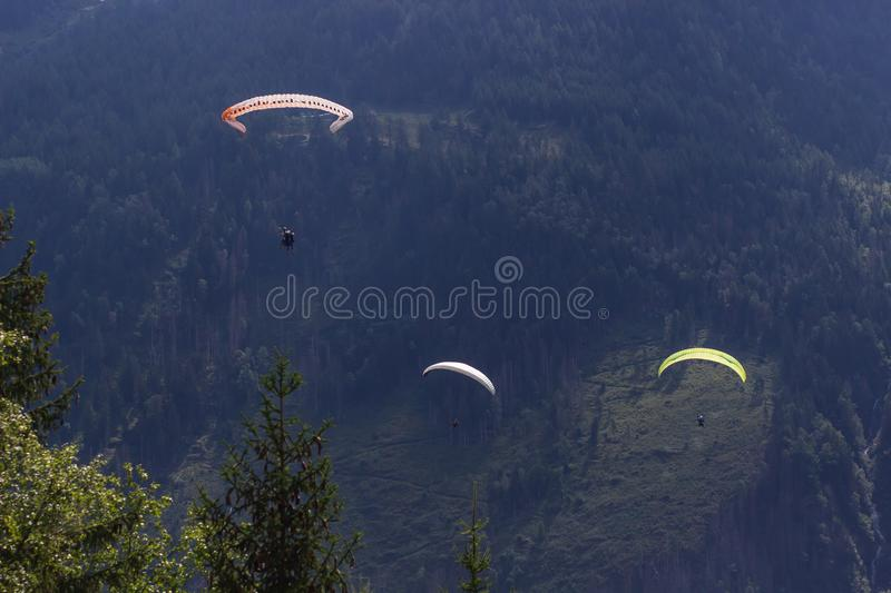 Paragliding flying over Mont Blanc Massif, in the background are Aiguilles du Chamonix, Alps, Chamonix, France royalty free stock image