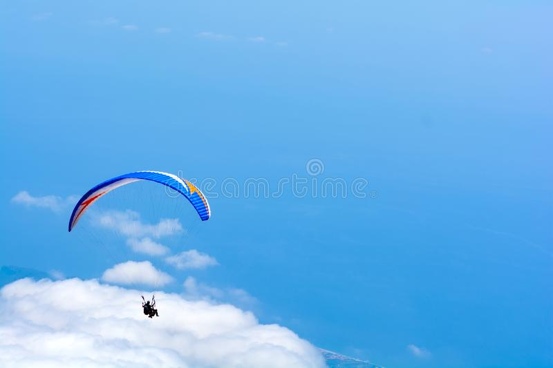 Paragliding flying in the sky over mountains and sea. Aerial view from Tahtali mountain, Turkey. Extreme sport or travel concept stock image