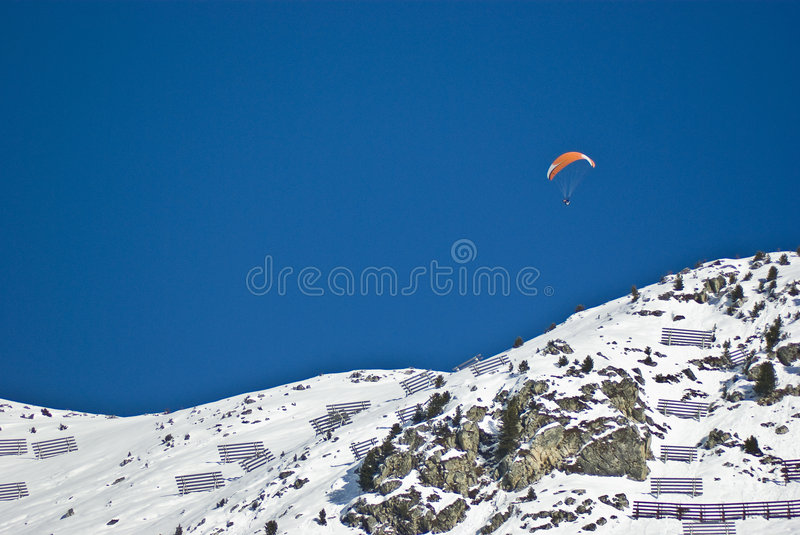 Paragliding freedom. Paraglider over verbier in the swiss alps on perfect crisp winters day, perspective compression from extreme telephoto lens stock photo
