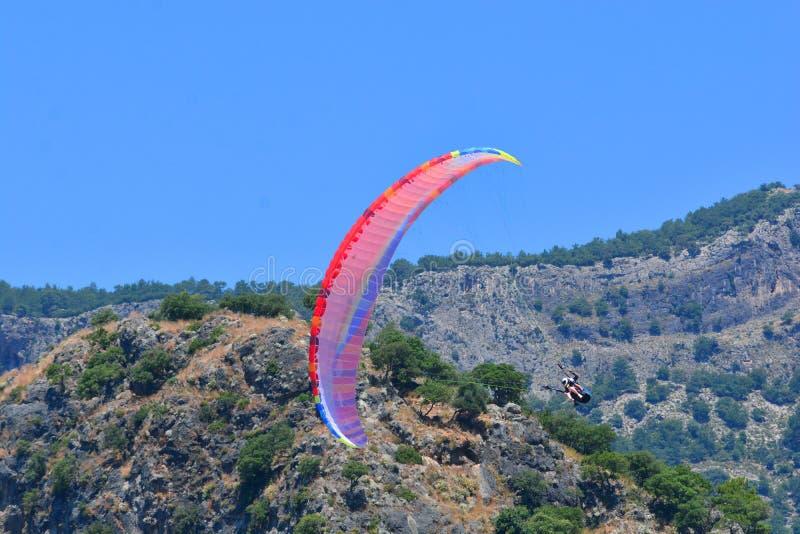 paragliding Gleitschirm auf einem blauer Himmel- und Gebirgshintergrund lizenzfreie stockfotografie