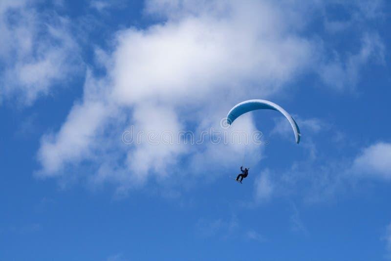 Paragliding i den blåa himlen med skidar royaltyfria bilder