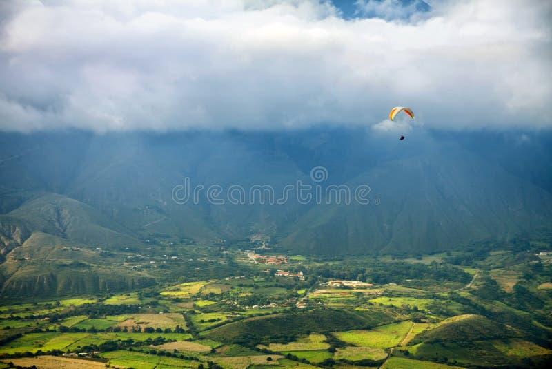 Paragliding i ovannämnda fält för berg och byar - sikt från luft arkivbilder