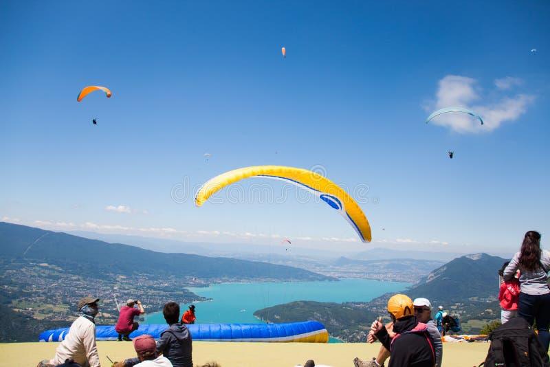 Paragliding instruktorzy Lata nad Annecy jeziorem i g?ra krajobrazem w niebieskim niebie zdjęcia royalty free