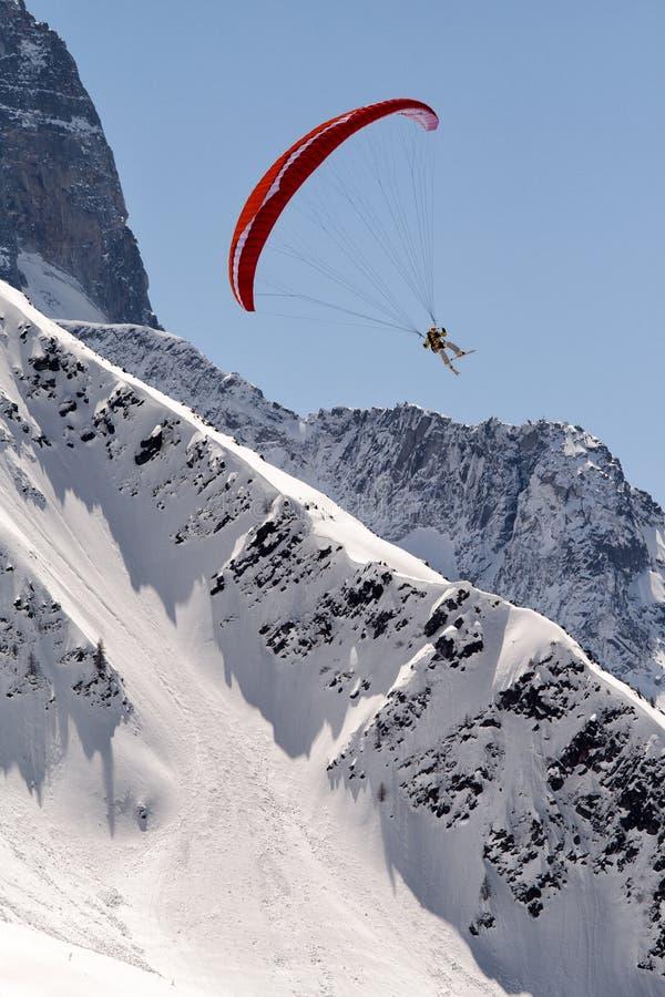 Paragliding ovanför snöig berg royaltyfria bilder