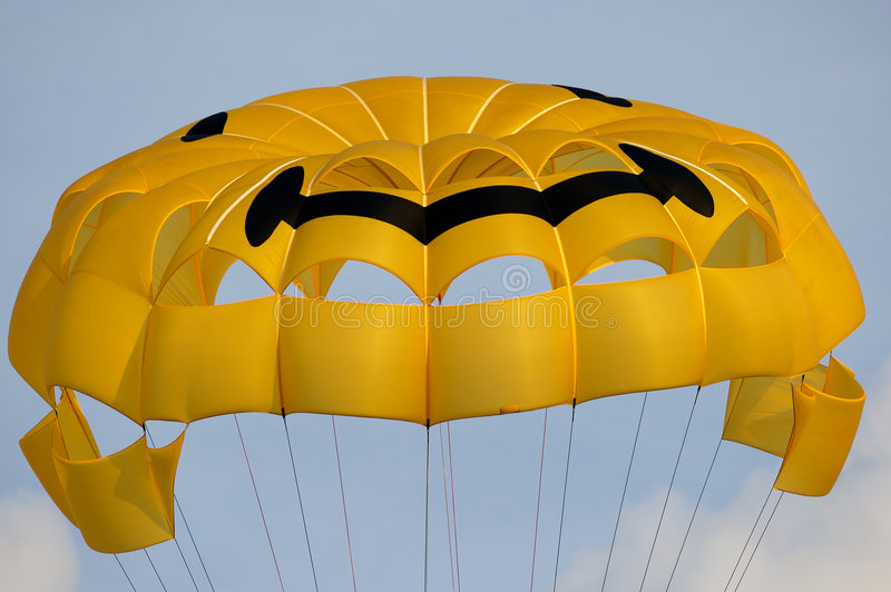 Paragliding Parachute. Closeup of a yellow paragliding parachute with a smiley face on it stock image