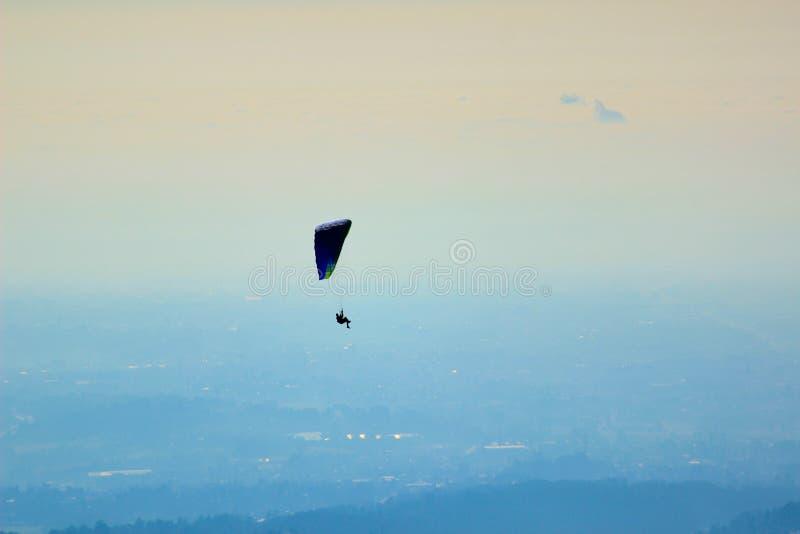Paragliding parachute Man fly sky blue royalty free stock photography