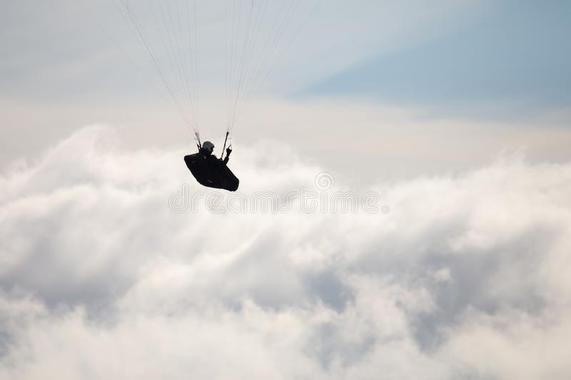 Paragliding pilot silhouette, above the fluffy clouds. stock photos