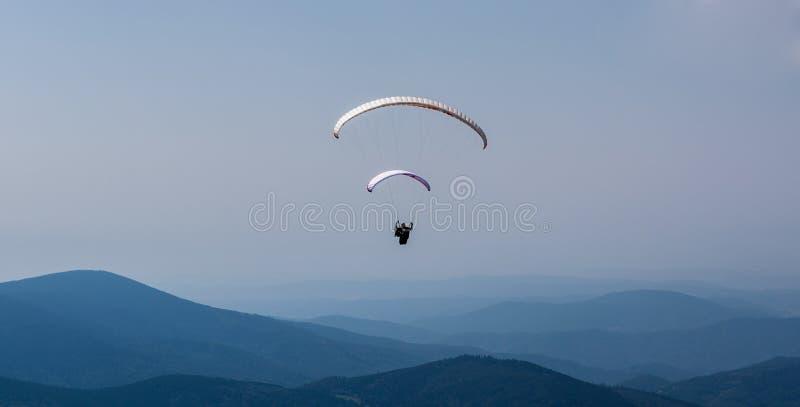Paragliding sobre la montaña contra el cielo azul imagen de archivo