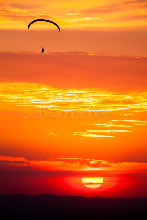 Paragliding in sunset. With orange sky and sun stock photography