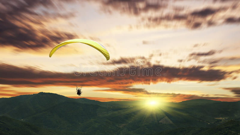 Paragliding at sunset with purple clouds. Paragliding at sunset with clouds stock images