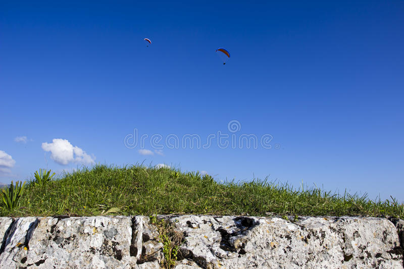 Paragliding. Two paraglider on blue sky. In the foreground stone and grass Look at my Landscape collection royalty free stock photography
