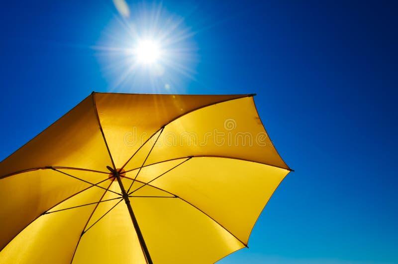 Paraguas amarillo con Sun brillante y el cielo azul imagen de archivo