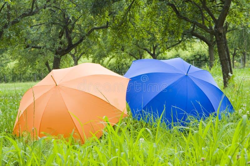 Paraguas anaranjados y azules foto de archivo