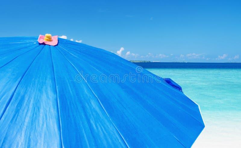 Paraguas azul en una playa arenosa tropical hermosa Conce del día de fiesta imagen de archivo