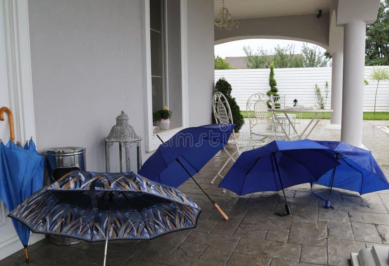 Paraguas azules abiertos en la terraza de un chalet de lujo con los muebles blancos del jardín y el piso blanco del pared y de pi fotografía de archivo libre de regalías
