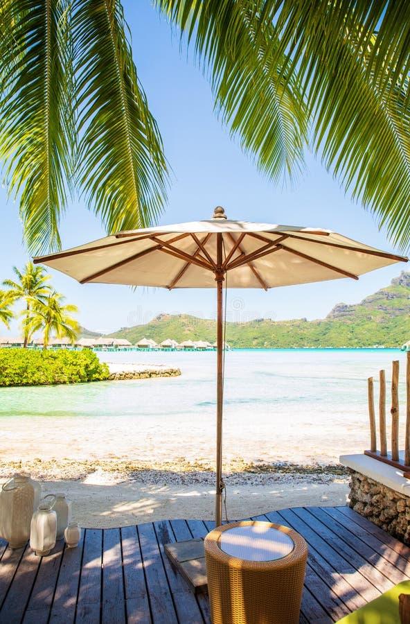 Paraguas blanco en decking de madera con la opinión del verano de la playa soleada de la isla de Bora Bora fotografía de archivo libre de regalías