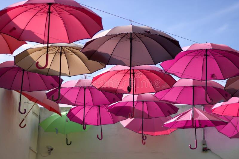 Paraguas coloreados púrpuras hermosos que cuelgan con el fondo del cielo azul imágenes de archivo libres de regalías